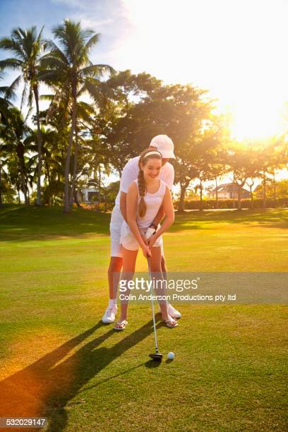 Caucasian golfer teaching granddaughter to play golf