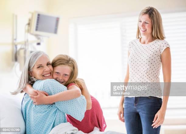 Caucasian granddaughter hugging grandmother in hospital
