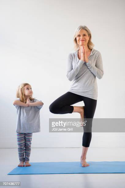 Caucasian granddaughter watching grandmother practicing yoga