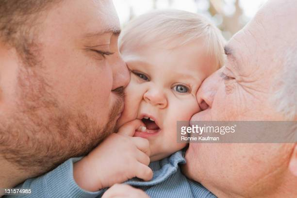 Caucasian grandfather and father kissing son