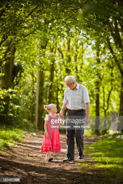 Caucasian grandfather and granddaughter walking in woods