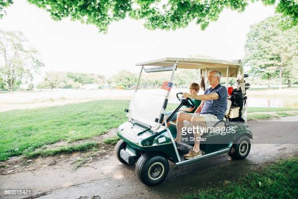 Caucasian grandfather and grandson driving golf cart on course