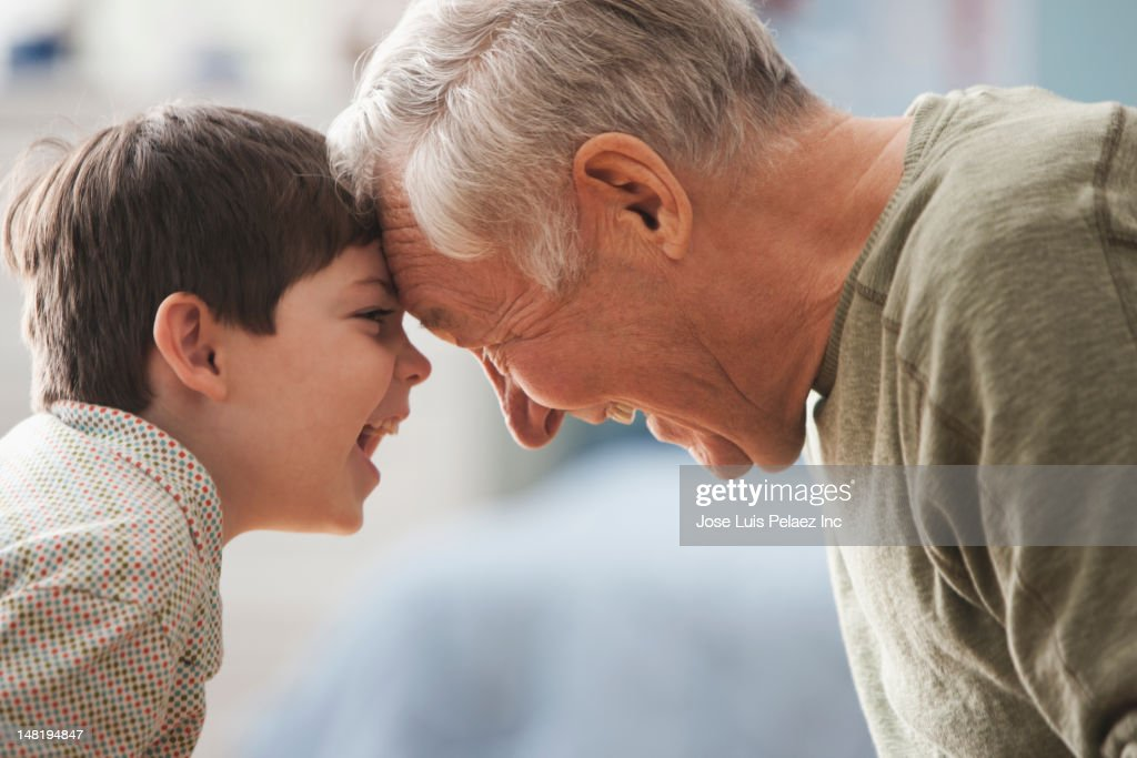 Caucasian grandfather and grandson looking at each other : Stock Photo