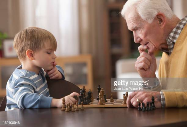 caucasian grandfather and grandson playing chess - chess bildbanksfoton och bilder