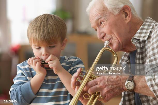 Caucasian grandfather and grandson playing instruments together