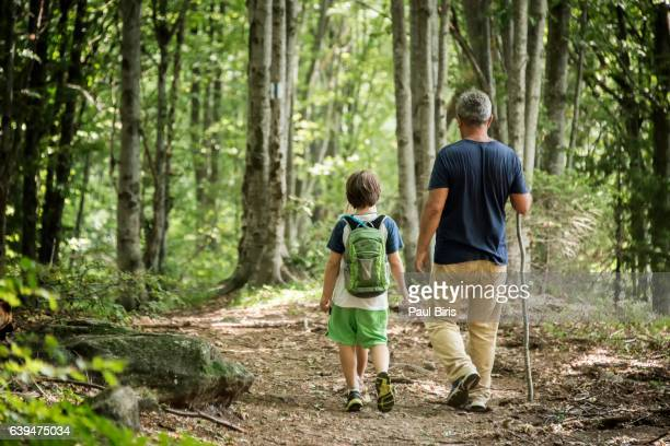 Caucasian grandfather and grandson walking in woods