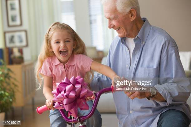 Caucasian grandfather giving granddaughter new bicycle