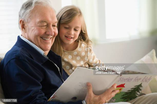 caucasian grandfather reading book to granddaughter - innocence stock pictures, royalty-free photos & images