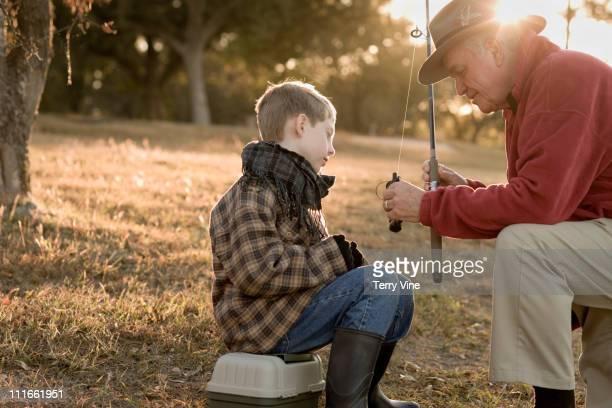 Caucasian grandfather teaching grandson to fish