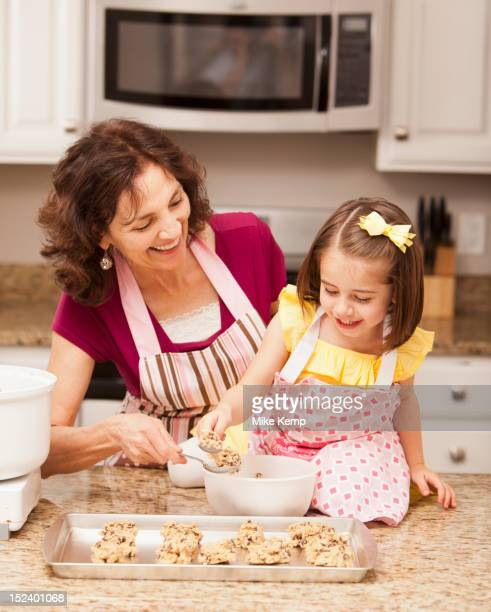 Caucasian grandmother and granddaughter baking cookies