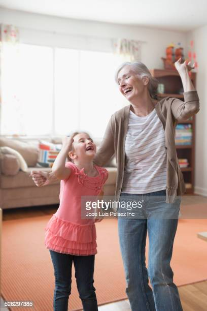 caucasian grandmother and granddaughter dancing in living room - west new york new jersey - fotografias e filmes do acervo
