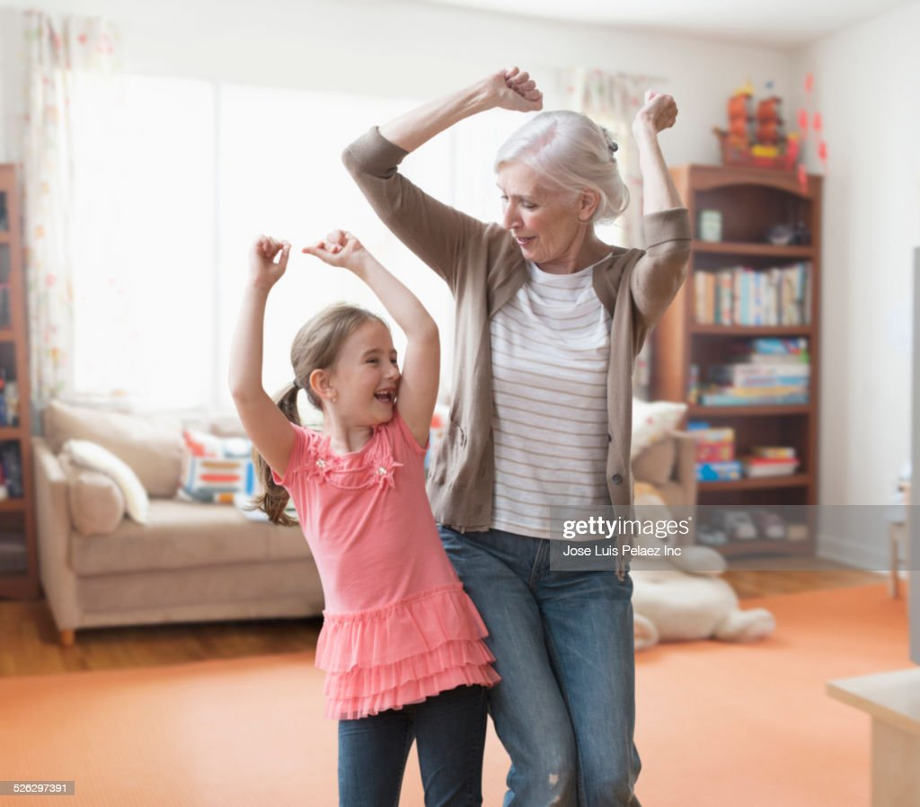 Caucasian grandmother and granddaughter dancing in living room : Stock Photo