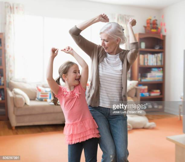 Caucasian grandmother and granddaughter dancing in living room