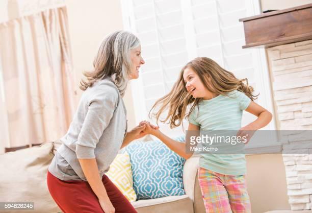 Caucasian grandmother and granddaughter dancing in living room