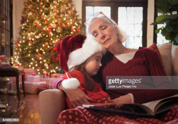 Caucasian grandmother and granddaughter napping on sofa