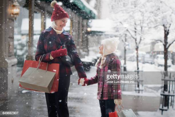Caucasian grandmother and granddaughter shopping in snow