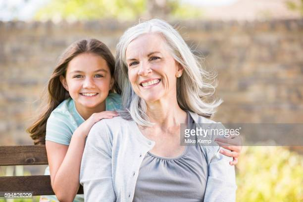 Caucasian grandmother and granddaughter smiling outdoors