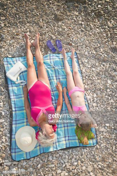 Caucasian grandmother and granddaughter sunbathing on beach
