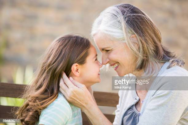 Caucasian grandmother and granddaughter touching noses