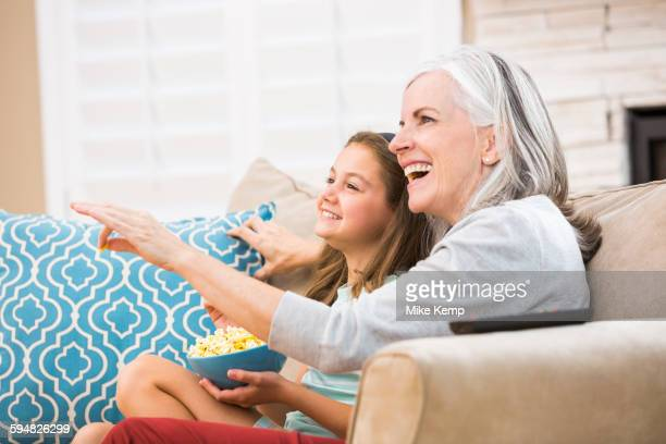 Caucasian grandmother and granddaughter watching television on sofa