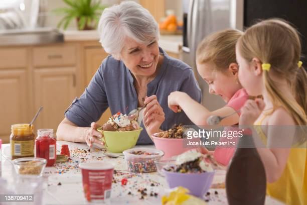 Caucasian grandmother and granddaughters making ice cream sundaes together
