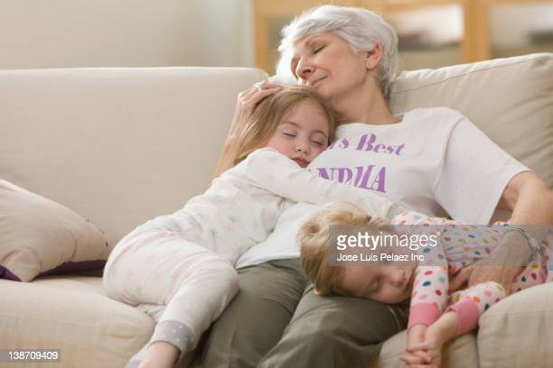 Caucasian grandmother and granddaughters napping on sofa together
