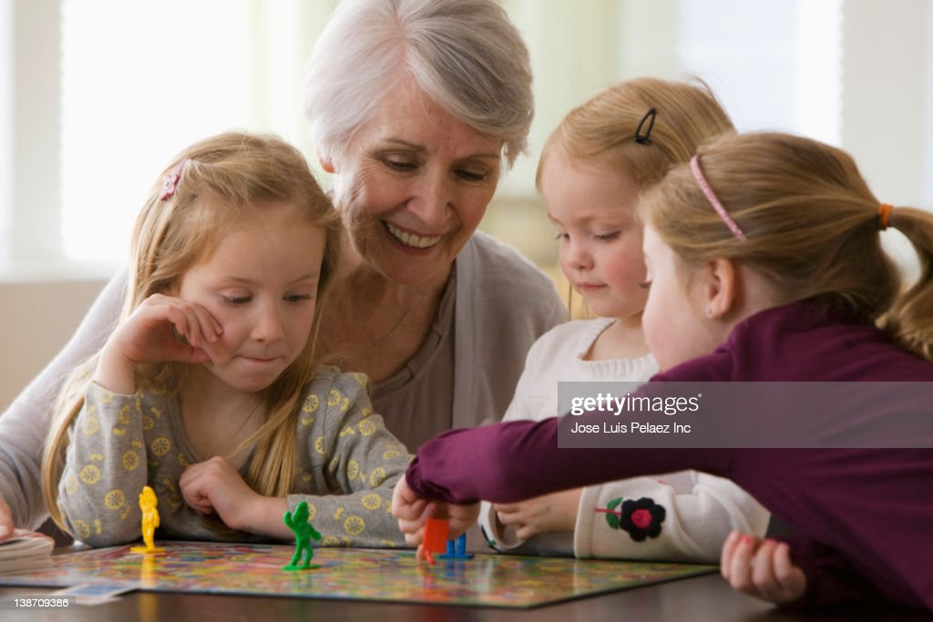 Caucasian grandmother and granddaughters playing game together : Stock Photo