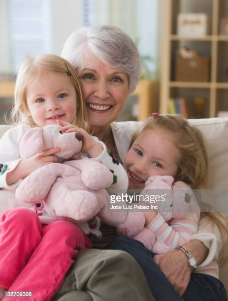 caucasian grandmother and granddaughters sitting on sofa together - west new york new jersey - fotografias e filmes do acervo