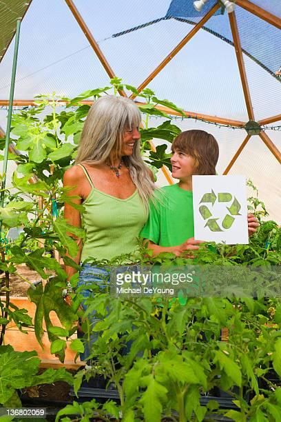 caucasian grandmother and grandson gardening - social awareness symbol stock photos and pictures