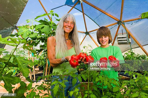 Caucasian grandmother and grandson holding tomatoes in garden