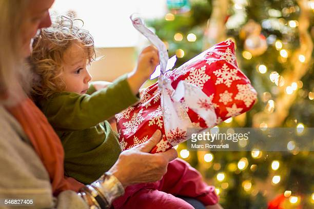 Caucasian grandmother and grandson opening presents near Christmas tree