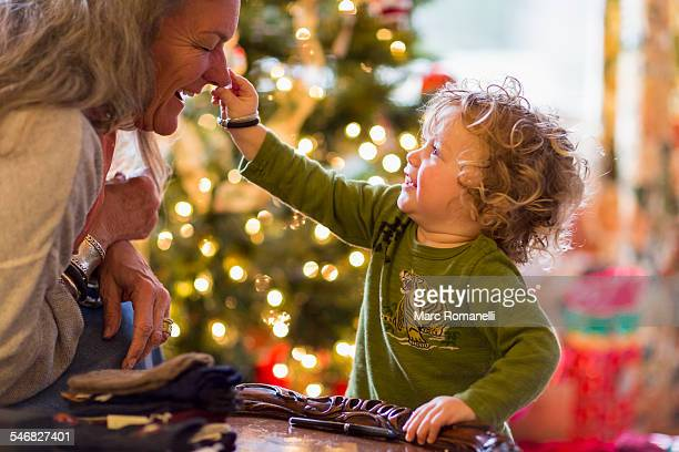Caucasian grandmother and grandson playing with toys near Christmas tree