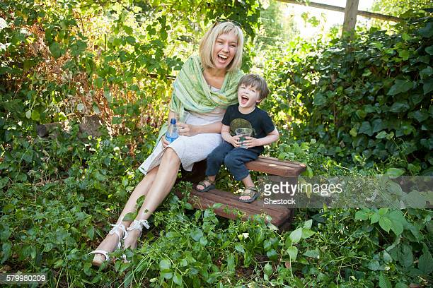 Caucasian grandmother and grandson sitting in garden