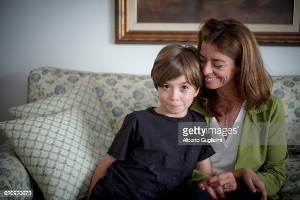 Caucasian grandmother and grandson sitting on sofa