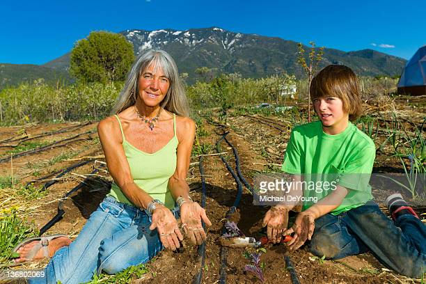 caucasian grandmother and grandson working in garden - kin in de hand stock pictures, royalty-free photos & images