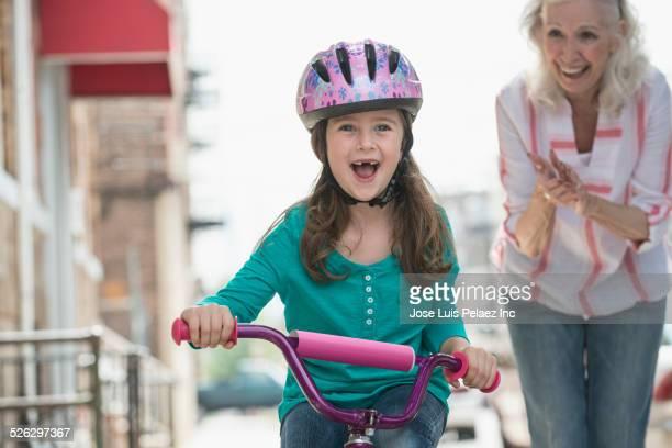 Caucasian grandmother teaching granddaughter to ride bicycle