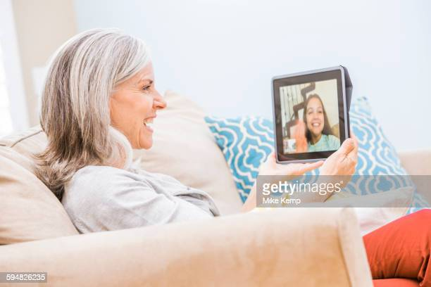 Caucasian grandmother videochatting with granddaughter on digital tablet