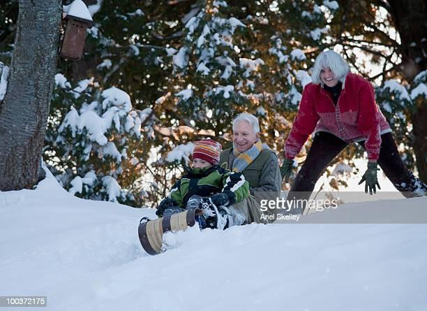 Caucasian grandparents with grandson sledding down hill