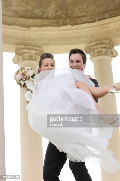 Caucasian groom carrying bride after wedding
