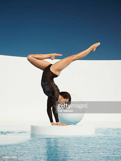 Caucasian gymnast performing hand stand on ice floe