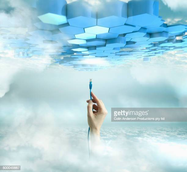 Caucasian hand holding cord in cloudy sky
