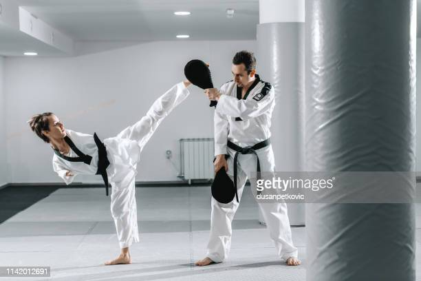Caucasian handicapped highly motivated girl practicing taekwondo with her training. Girl kicking kick target.