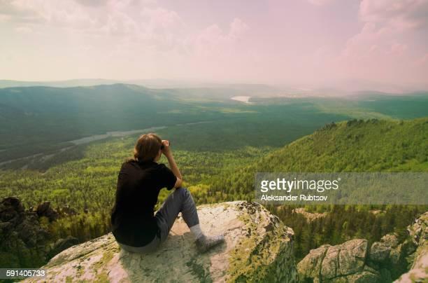 Caucasian hiker admiring remote landscape from rocky hilltop