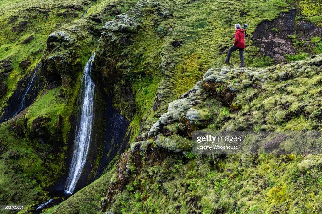 Caucasian hiker admiring waterfall and rock formations on mountainside : Foto stock