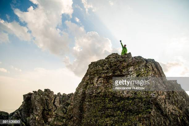 caucasian hiker cheering on rocky hilltop - summits russia 2015 stock pictures, royalty-free photos & images
