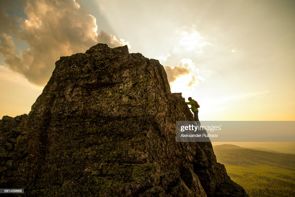 Caucasian hiker climbing on rock formation : Foto de stock