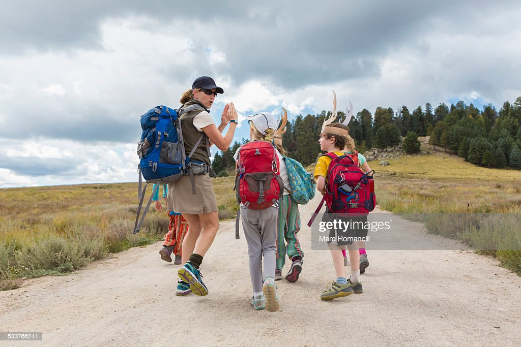 Caucasian hiker leading children on path in remote landscape : Foto stock
