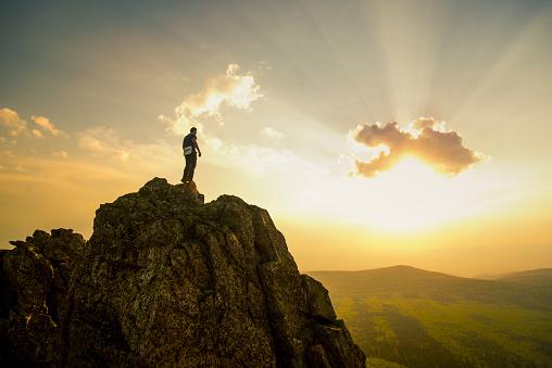 Caucasian hiker on rocky hilltop in remote landscape - gettyimageskorea