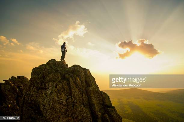 caucasian hiker on rocky hilltop in remote landscape - mountain peak stock pictures, royalty-free photos & images