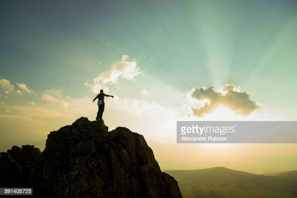 caucasian hiker on rocky hilltop in remote landscape - summits russia 2015 stock pictures, royalty-free photos & images